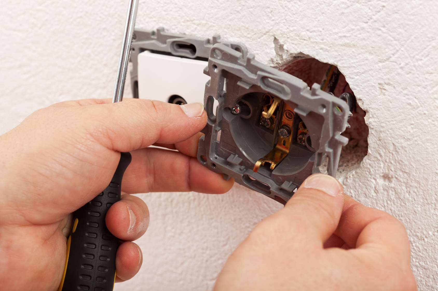 Electrician hands mounting electric wall receptacle - fitting into place